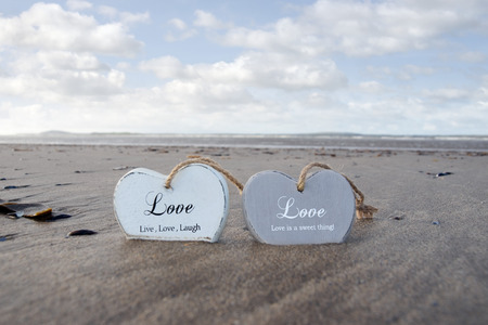 two inscribed wooden love hearts in the sand on a wild Atlantic way Irish beach in summer photo