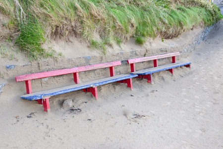 bench covered in sand from the winter storms in Ireland photo