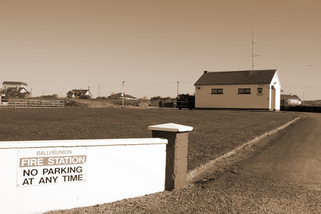 Ballybunion fire station with fire truck parked outside in sepia