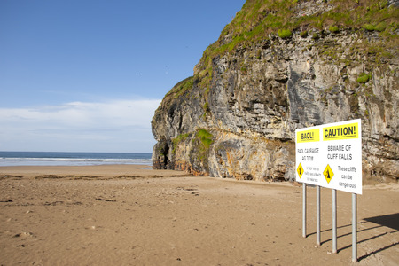 gaelic: beware of land falls warning sign beside the cliffs in Ballybunion county Kerry Ireland in English and Gaelic