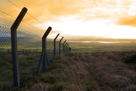 barbed wire fence: barbed wire fencing protecting a site on the Knockanore hill in Ballybunion county Kerry Ireland Stock Photo