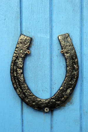 black horseshoe nailed to blue painted wooden boards on a door or wall photo