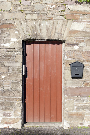 youghal: brown wooden doorway and a post box on old stone wall