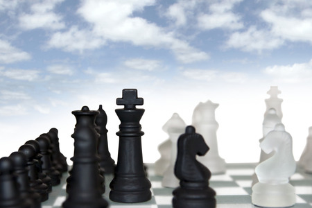 chess pieces isolated against a cloudy blue sky background photo