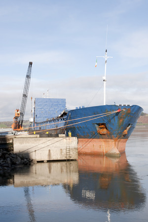 youghal: large ship being loaded with steel by crane at Youghal pier county Cork, Ireland