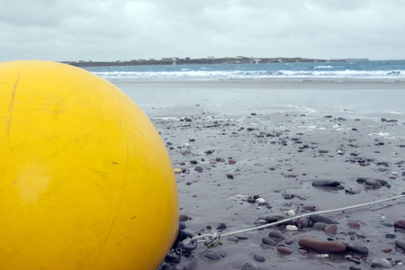 giant yellow buoy on a beach in the wild atlantic way photo