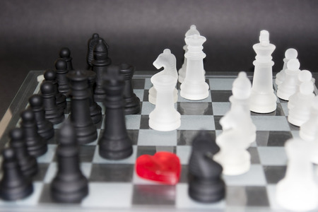 love heart in the centre of a chess board with pieces photo