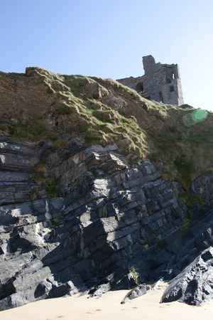 old historic castle on a cliff edge over the beach in Ballybunion county Kerry Ireland photo