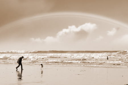 one man and his dog on Ballybunion beach county Kerry Ireland with a rainbow in sepia photo