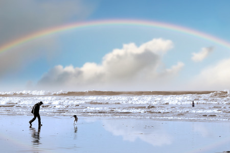 one man and his dog on Ballybunion beach county Kerry Ireland with a rainbow photo