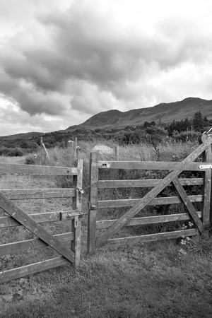 padlocked: chained fence with mountains at the background in black and white