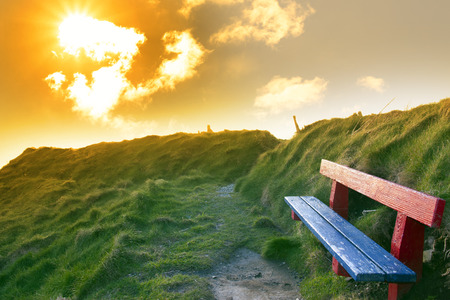 bench on a cliff edge with views of Ballybunion beach and coast at sunset