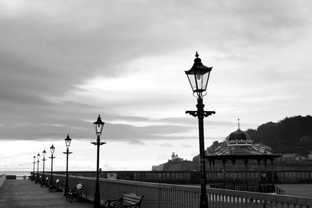 youghal: row of vintage lamps on the promenade in Youghal county Cork Ireland in black and white Stock Photo