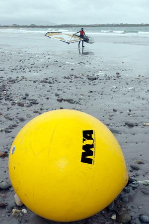 windsurf: gigante asociaci�n windsurf irland�s boya amarilla en una playa en el camino atl�ntico salvaje Foto de archivo