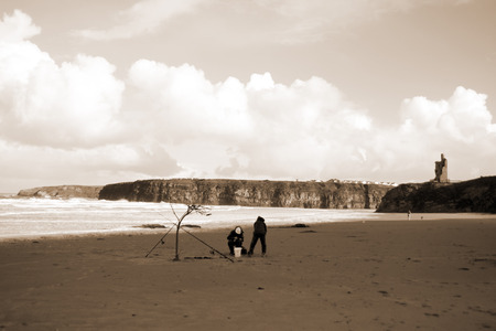 two men with fishing rods supported by a branch in the sand on a beach in Kerry, Ireland photo