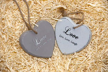 string together: two grey wooden love hearts  in a love nest made of straw with loving inscriptions