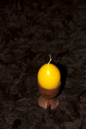 egg cup: unlit yellow egg shaped candle in an egg cup on a brown carpet