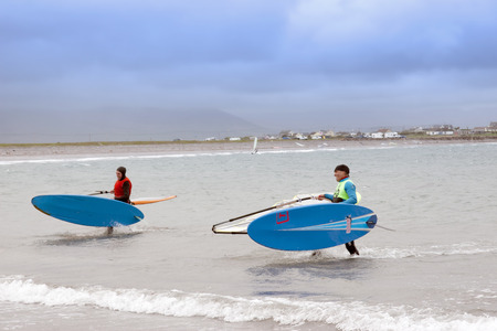 windsurfers: windsurfers finishing up after race and surf on the beach in the maharees county kerry ireland