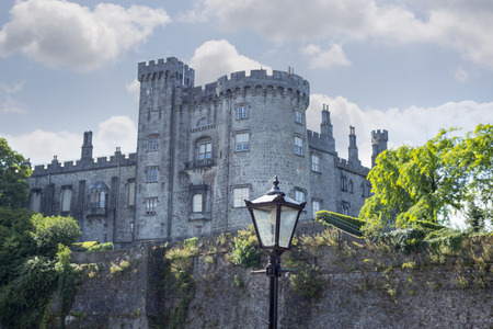 irish history: beautiful antique street lamp and riverside view of kilkenny castle in ireland