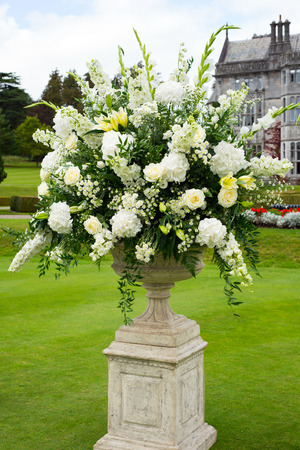 urn of opulent bouquet of flowers in manor gardens