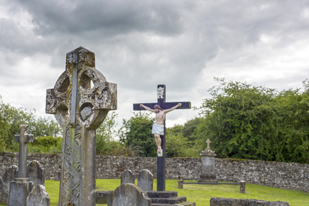irish easter: celtic cross headstone and crucifix in a graveyard in county tipperary ireland