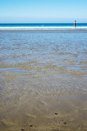 lashing: calm soft waves lashing onto ballybunion beach in county kerry ireland with wading woman