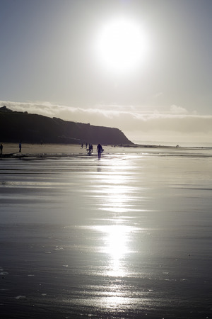 ballybunion: silhouette of surfer and people out for a walk as the sun sets in Ballybunion county Kerry Ireland