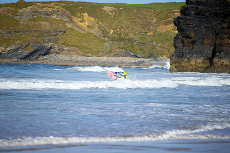 canoeist: bright winter view of kayaker at ballybunion beach and cliffs on the wild atlantic way in ireland