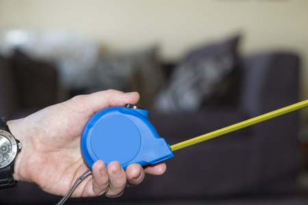 do it yourself: measuring tape in hand for do it yourself home improvements Stock Photo