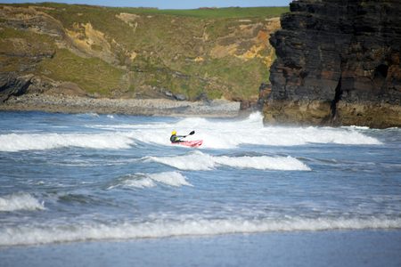kayaker: bright winter view of kayaker at ballybunion beach and cliffs on the wild atlantic way in ireland