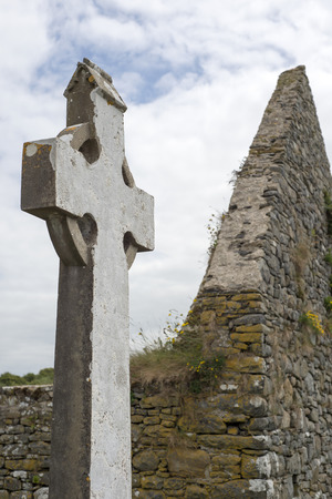 church ruins: old celtic cross head stone from a grave yard in county kerry ireland next to church ruins