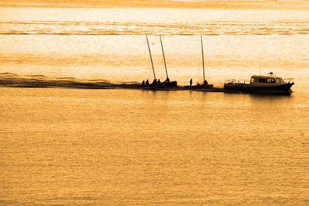 towed: boats being towed in cobh ireland at sunset