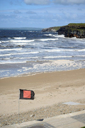 quicksilver: quicksilver flag flying beside surf school with ballybunionbeach and cliffs in background
