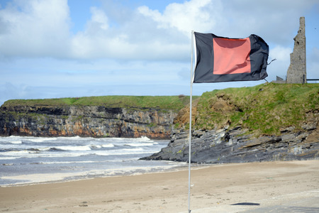 quicksilver: quicksilver flag flying beside surf school with ballybunion castle in background Stock Photo