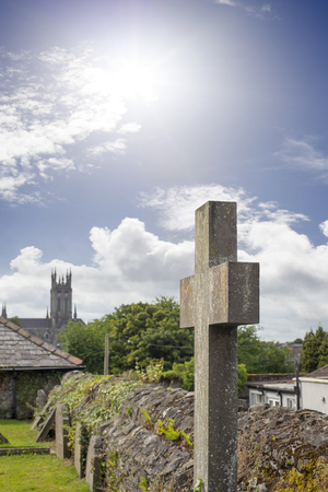 ancient ireland celtic cross: sunshine over cross at ancient graveyard in St Canice�??s Cathedral in kilkenny city ireland