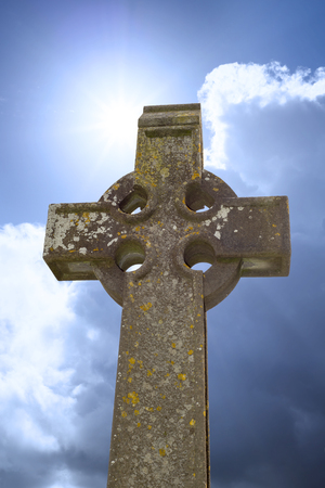 sunshine over celtic cross at ancient graveyard in St Caniceâ??s Cathedral in kilkenny city ireland