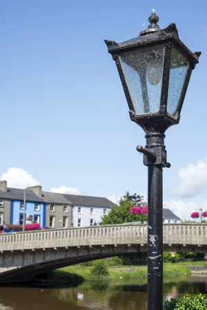 beautiful antique street lamp and riverside view of town and bridge
