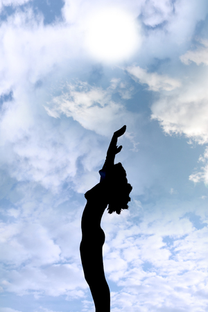 attractive silhouetted nude woman holding her hands up to the sky giving gratitude to the heavens in a yoga pose with a cloudy background photo