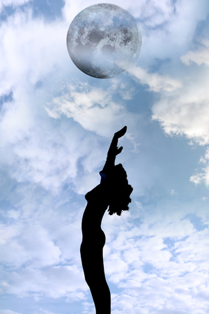 attractive silhouetted nude woman holding her hands up to the sky giving gratitude to the moon in a yoga pose with a cloudy background photo