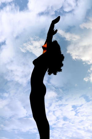 attractive silhouetted woman holding her hands up to the sky giving gratitude to the heavens in a yoga pose with a cloudy background