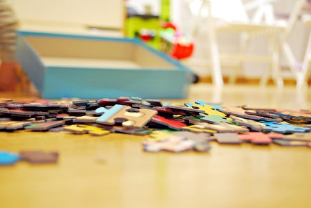 Childrens puzzle scattered on a wooden table Stock Photo