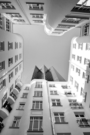 property management: Tenement house on the background of a modern office building.Black and white Stock Photo
