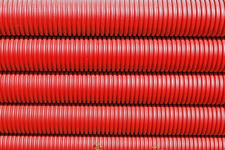 Red plastic tubes in the warehouse. Stock Photo
