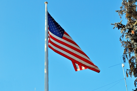 The American flag waving in blue sky