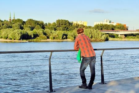 Man standing behind looking at river.