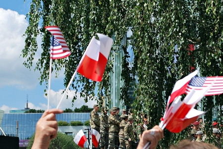 protestors: Warsaw, Poland. 6 July 2017. President Donald Trump speaks to the People of Poland.Crowd enthusiastically wave flags