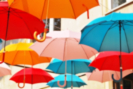The background is a multi-colored umbrella, blurred beautifully Фото со стока