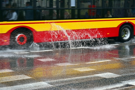 Splashes from under the heavy rain. Blurred bus.