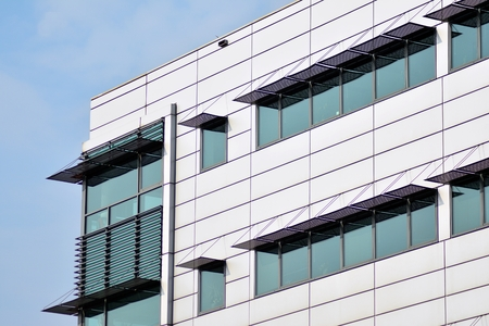 Abstract fragment of contemporary architecture, walls made of glass and concrete. Glass curtain wall of modern office building