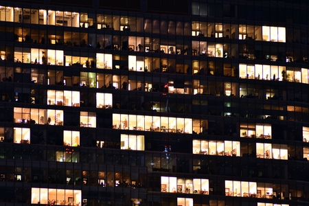 Office building at night. Late night at work. Glass curtain wall office building Banco de Imagens